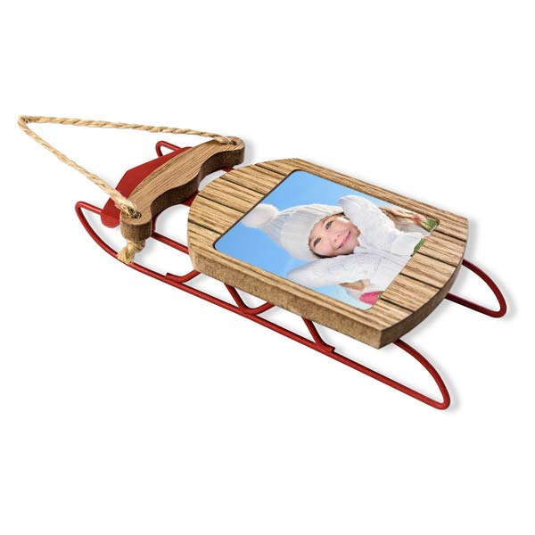 Create your own photo ornament with our red metal and wood sled and add interest to your tree